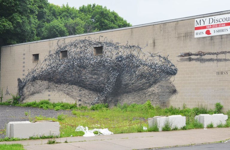 Wall Therapy mural in Rochester, on the side of a building, a long whale in grey and black