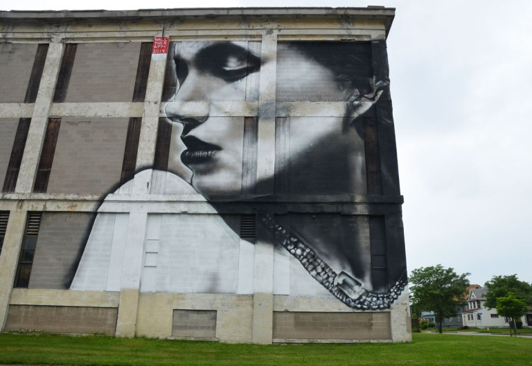 Wall Therapy mural in Rochester, on the side of a building, a three storey high black and grey woman looking over her shoulder