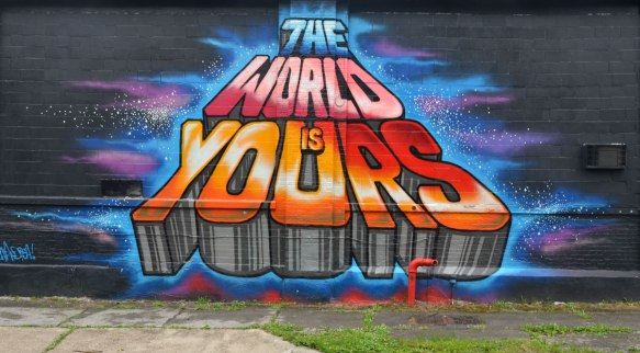 "Wall Therapy mural in Rochester, on the side of a building, colourful words in capital letters that say ""The world is yours"" in blue, pink, and red, and orange"