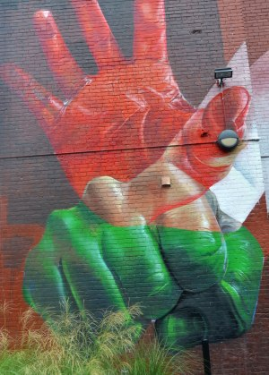 part of a larger mural - two hands, a red open hand and below it a closed green fist