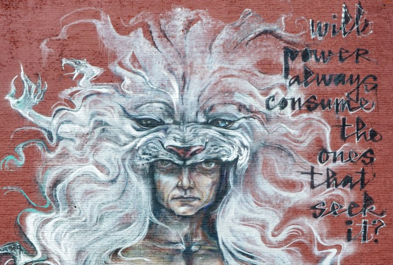 top part of a tall mural showing a man's head with a white creature covering his head and looking like long wavy hair. With the word 'Will power always consume the ones that seek it?'