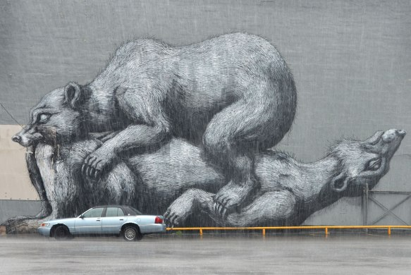 Black and white and grey mural, very large, on the side of a building by a parking lot by ROA featuring 2 bears, one on top of the other. A car is parked in front of the mural. It is raining.