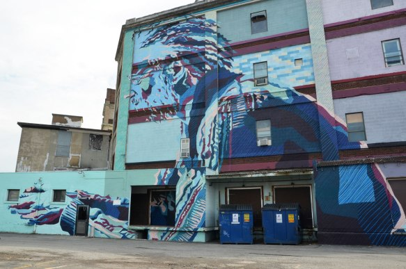 A large four storey mural of a man, upper body, in profile, in blues and purples. His hands are in front of him.