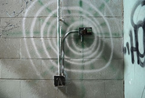 a large spiral made with spray paint on a concrete block wall