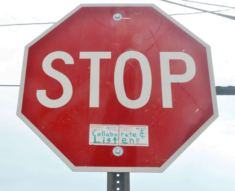 stop sign to which someone has added a sticker that says collaborate and listen