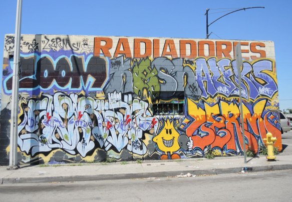the side of a building is covered with graffiti, mostly tags, but one little yellow creature with a two little orange legs. Also the word Radiadores in large red letters
