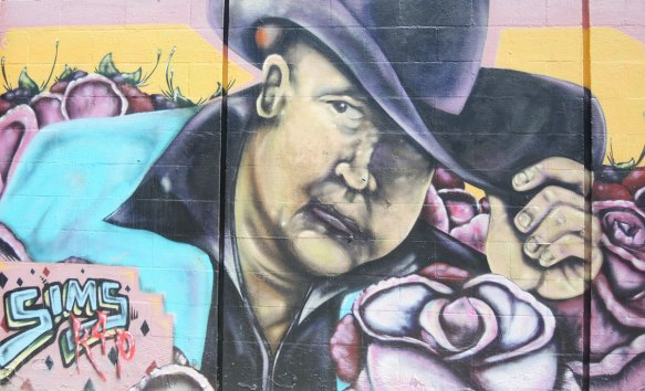 street art portrait of a man with a large derby hat and surrounded by large pink roses