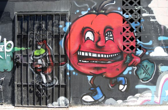 greedy red tomato guy, a large red tomato with a face, dollar signs in one eye, large blue sneakers on skinny legs, and he's holding a bag of money
