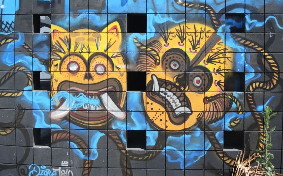 street art of two yellow animal masks, one is feline and the other may be monkey. South American looking in the design and markings on the masks.