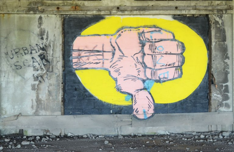 large pink hand giving a thumbs down sign, graffiti on a wall. the words Urban scar have been written beside it. The hand is in a large yellow oval shape