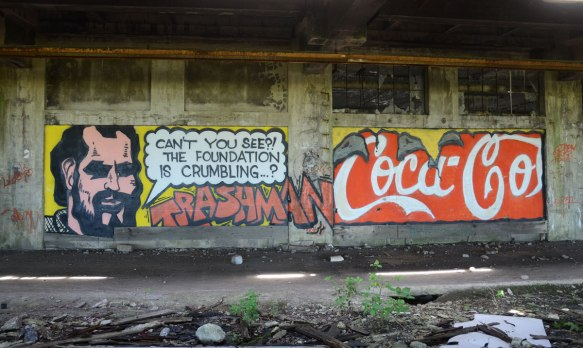 graffiti painting - a man with the words Can't you see? The foundation is crumbling. Trashman is written in large red letters, also a mock coca-cola logo