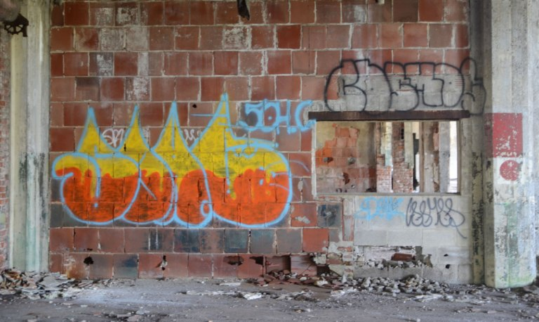 broken brick wall with an orange and yellow bright tag on it.