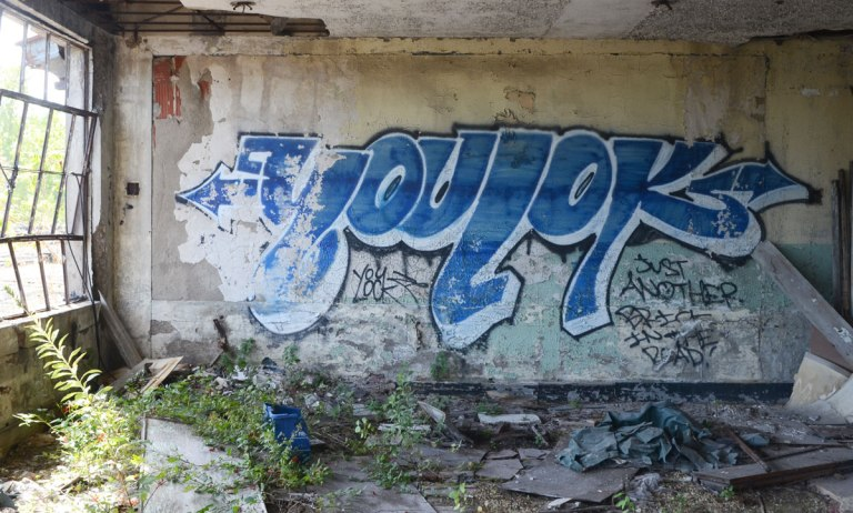 a blue tag that says youlok on a wall in an abandoned building