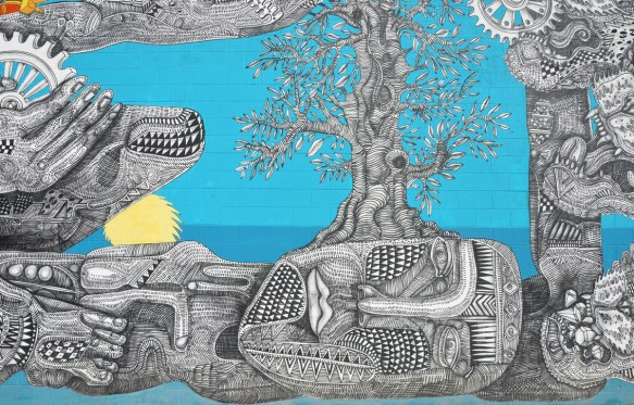 part of a large mural by Zig Ziegler on a wall, intricate black line drawings on white of faces, people like creatures, trees, skulls, gears, feets, etc. on a sky blue background. Some yellow and orange features for contrast, sun, hair, circles - a person lying on the ground with eyes closed, a tree is growing upwards from the side of the head