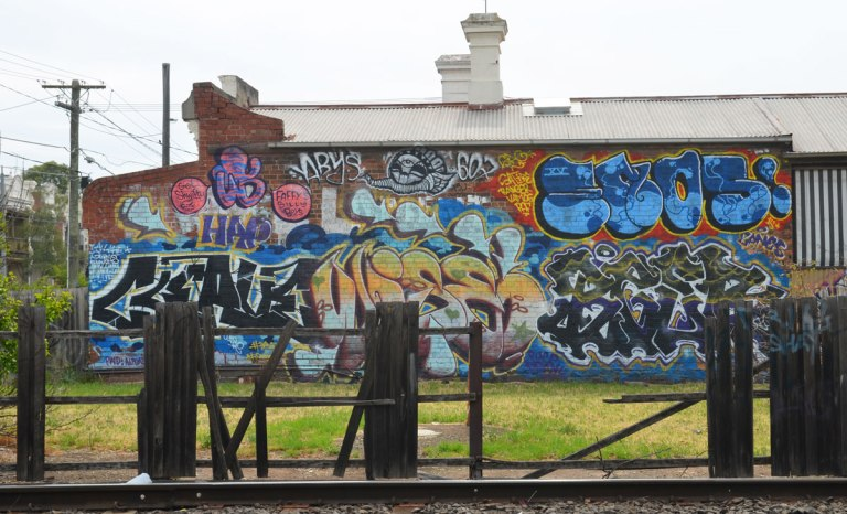 looking across the train tracks to a side of a building that has been covered with street art