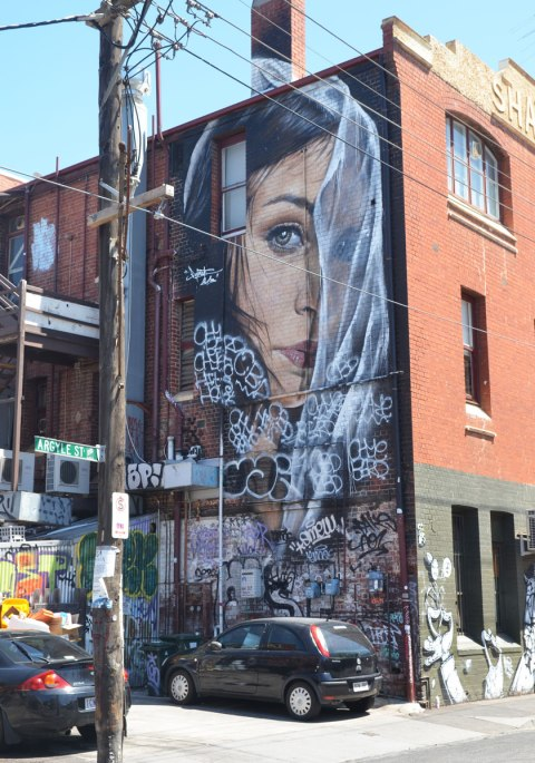 A mural by Adnate on Argyle Street of a woman's head, partially in profile, and partially hidden behind a thin white veil