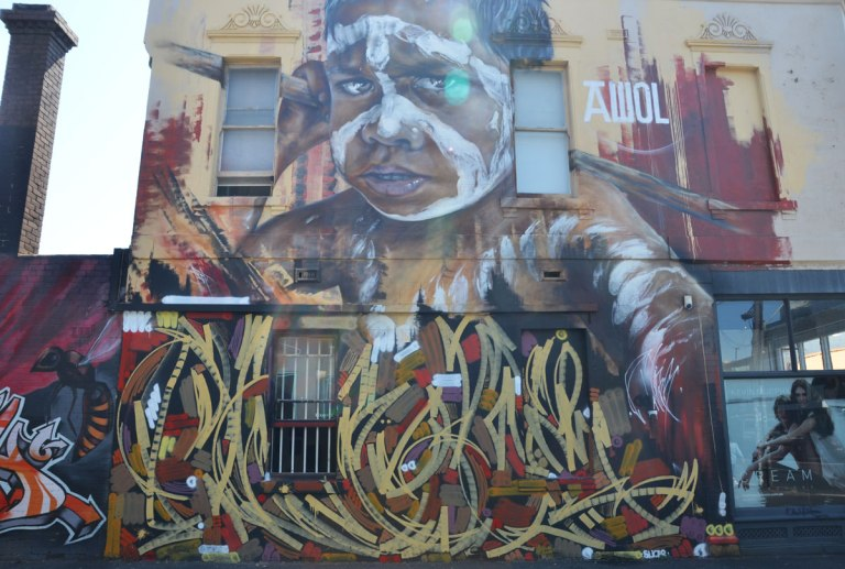 Large mural of the face of an Australian aboriginal boy painted by Adnate in Melbourne, on the side of a two storey building.
