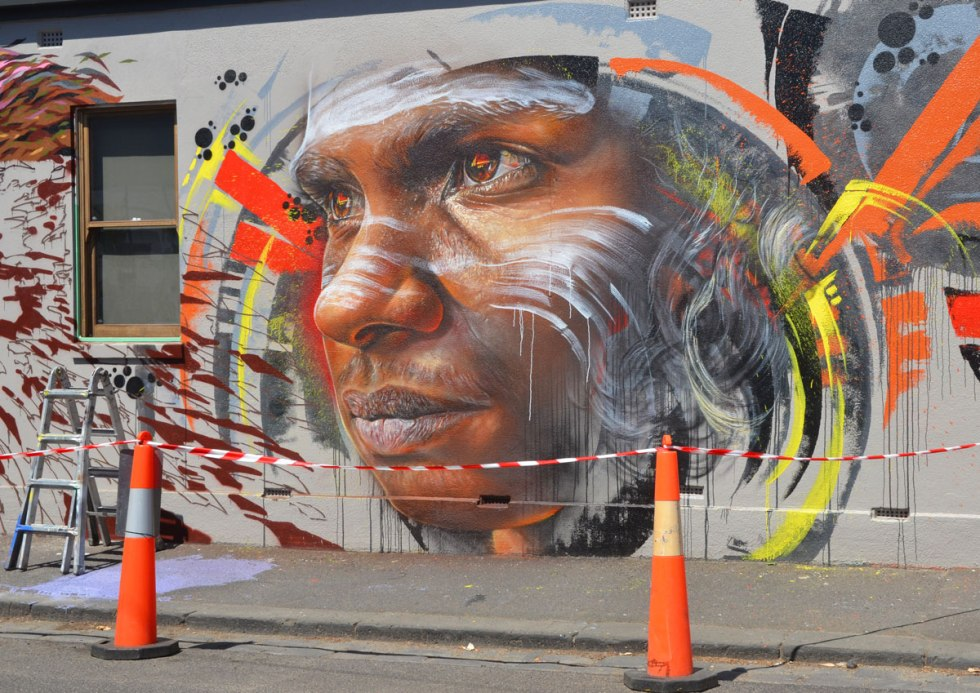 part of a larger mural, a street art painting of an aboriginal young man's face with white markings on his face, newly painted by Adnate in Melbourne (Fitzroy) with orange cones in front so that people don't walk in front of it.