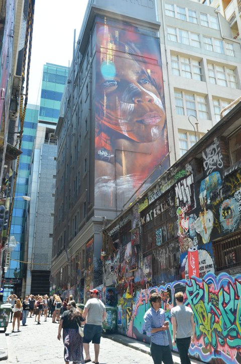 Large mural of the face of an Australian aboriginal boy painted by Adnate in Melbourne - high on a wall overlooking Hosier Lane and all it's graffiti and tourists.