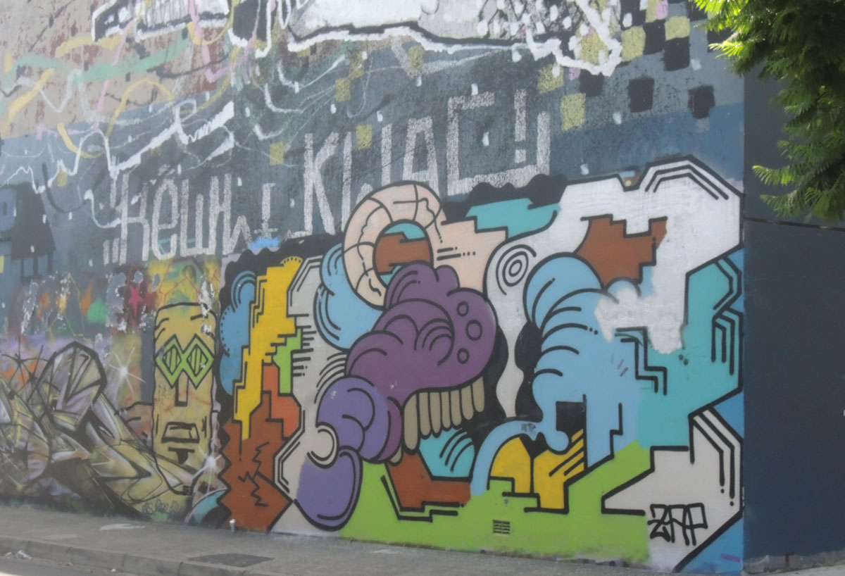 mural of blobs and shapes in different colours on a wall in an alley