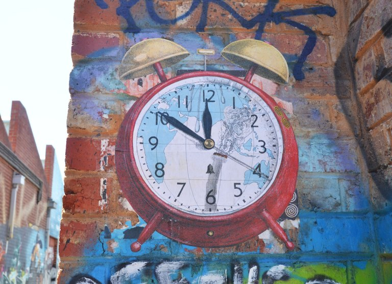 paste-up paper of an old fashioned round red alarm clock with two gold ringers on the top. The face of the clock has a map on it. the time is 11:50