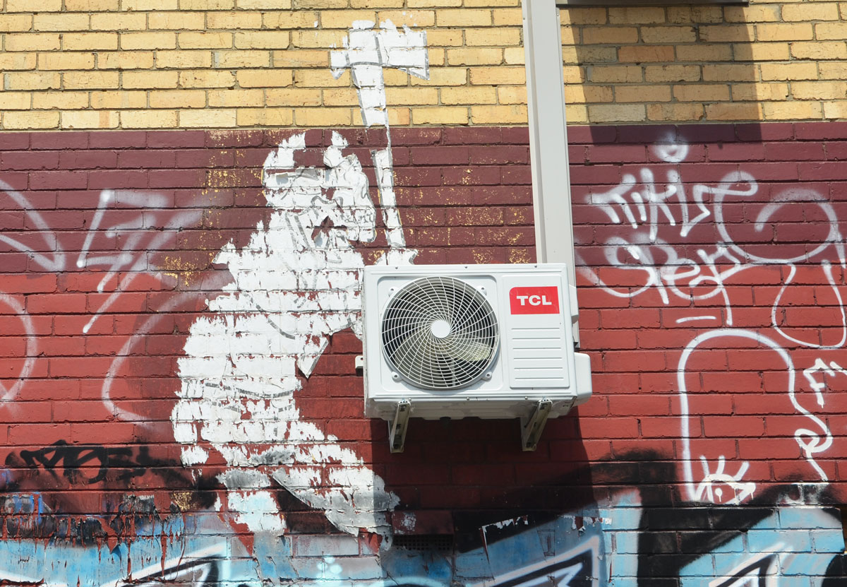 old wheatpaste that is peeling off the wall. It was a person holding an ax over its head and it looks like it is attacking a real air conditioner that is mounted on the wall.