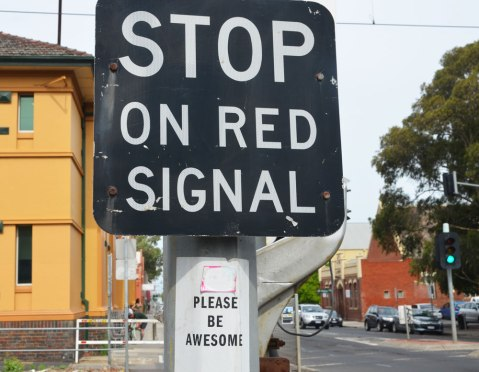 sign at a railway crossing that says Stop on Red Signal. below it someone has posted a sign that says Please be awesome.
