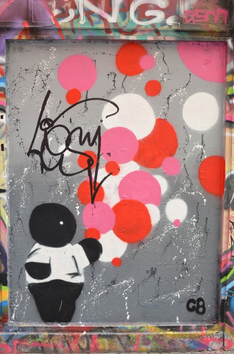on a grey metal door in an alley, a simplistic painting of a chubby black boy wearing a white shirt and holding a bunch of white, pink, and red balloons, some of the balloons are drifting away.