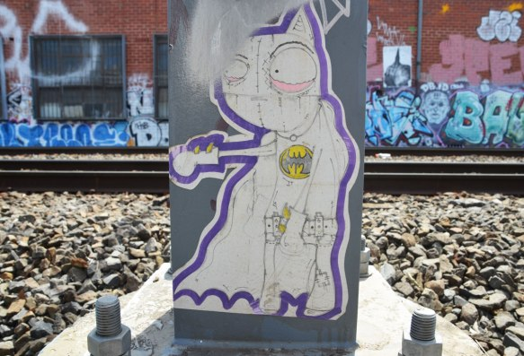 wheatpaste on a metal box that is bolted to a concrete block beside the railway tracks. The picture is on white, black line drawing of a cat on two legs, outlined in purple. Cat is wearing a jacket with batman logo on it, also belt and one glove . Not a real cat, but drawn to look like a cat that has been sewn together with fabric - stitches in the face,