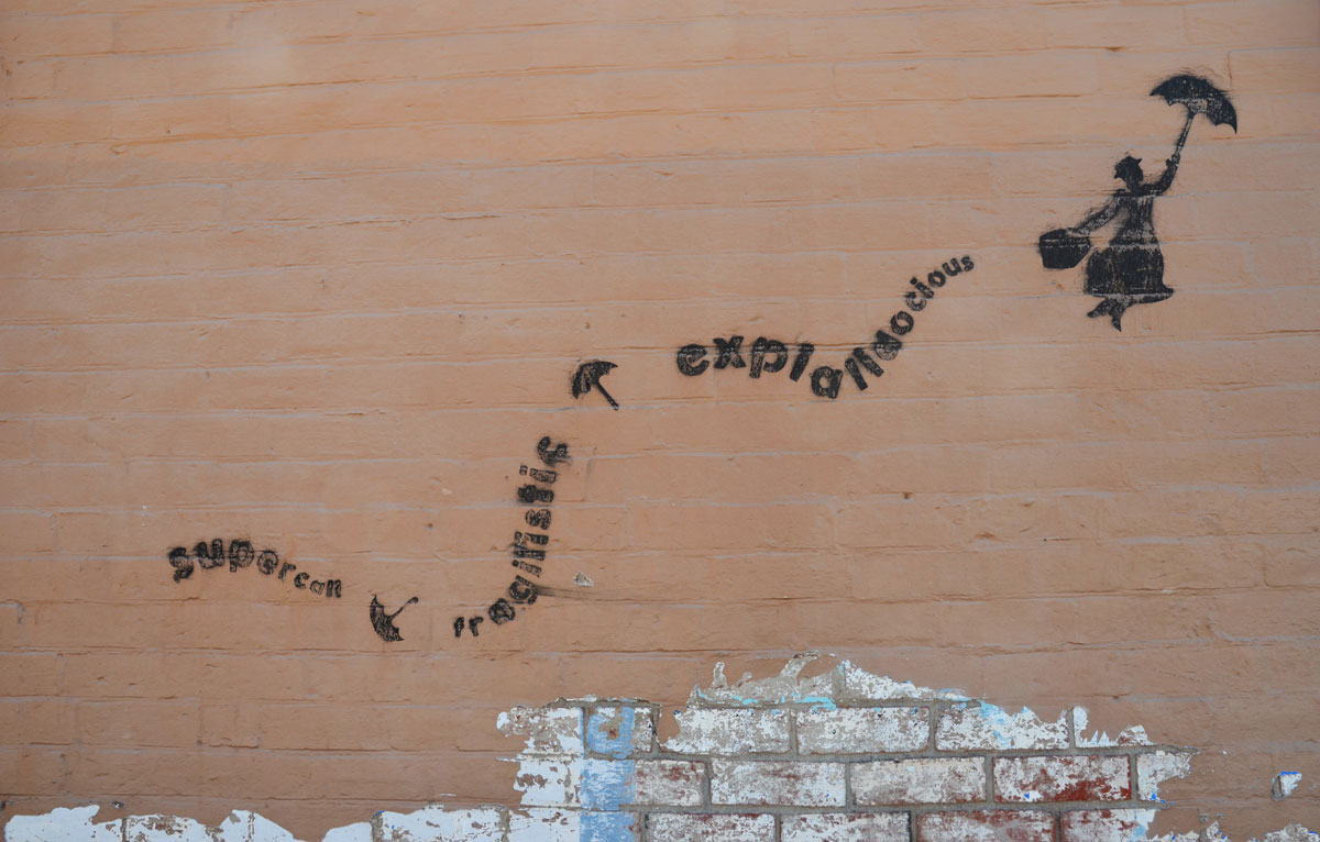 black stencil on a light brown wall, Mary Poppins floating upwards with her open umbrella. Her trail is the word supercalifragiliciousexpialidocius.