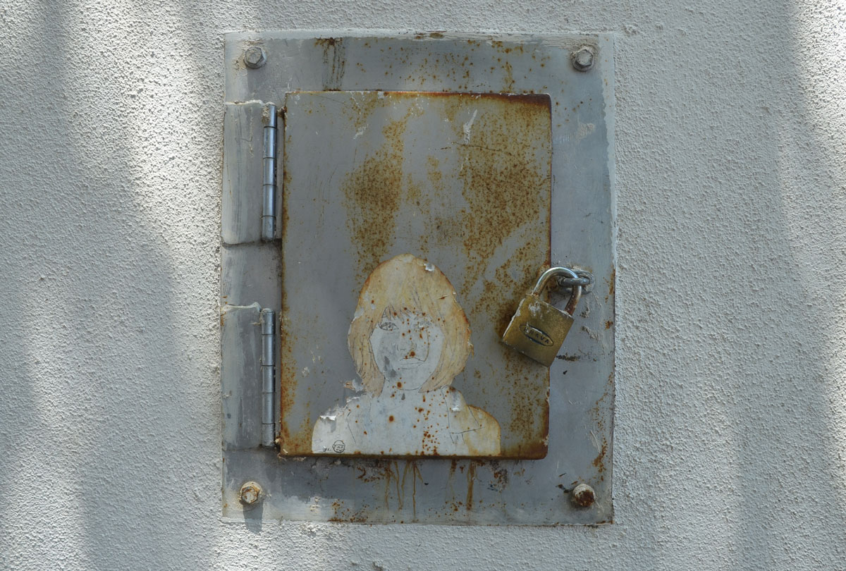 small paper wheatpaste of a blond woman on the door of a small metal box, with a padlock. The paper is peeling a bit and the rust from the box is also on the graffiti