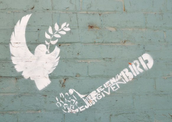 "a white stencil on a blue wall, a dove in flight with an olive branch in its mouth. A hand and arm is made of the words ""You have just been given the bird"""