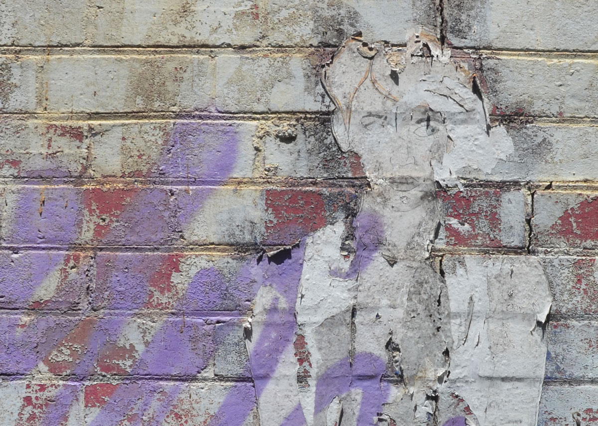 Paper wheatpaste of a woman that is badly faded and peeled off. She is beside some purple spray paint.