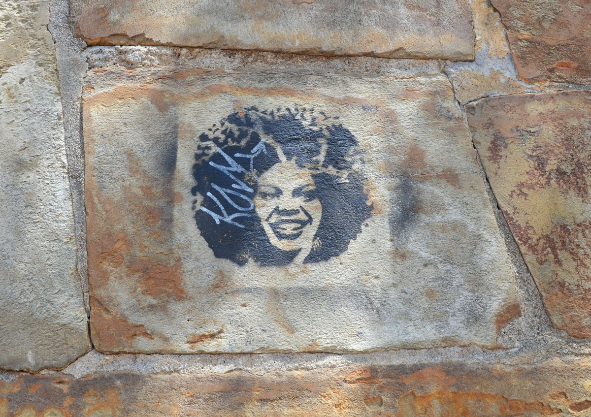 black stencil on a stone wall of a woman's head, very large Afro hair style, smiling,
