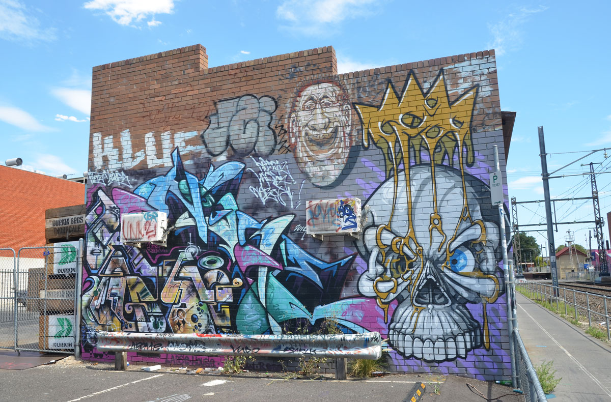 A wall of a brick building beside a train track. It is covered with street art including a very large skull with a gold crown tied to it, a laughing man's face, and a lot of geometrics.