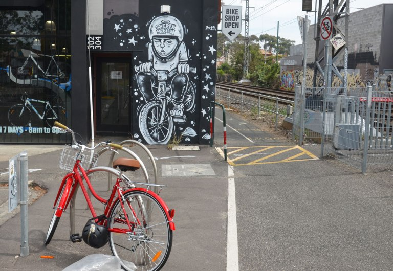 a red bicycle is parked outside a bike shop that has a painting of a person on bicycle by the door. It is beside a bike path and the train tracks.