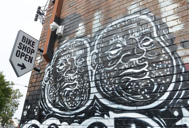 street art painting of two fat men's faces, white line drawing on black background, on a wall beside a sign that says Bike Shop