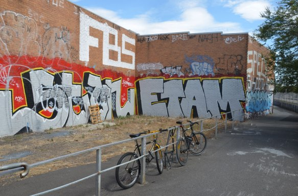two bikes parked against a metal railing beside a bike path. on the other side of the railing is a two storey L shaped brick building with the lower level covered with two large tags, one says ETAM. FBS is written on the second storey.