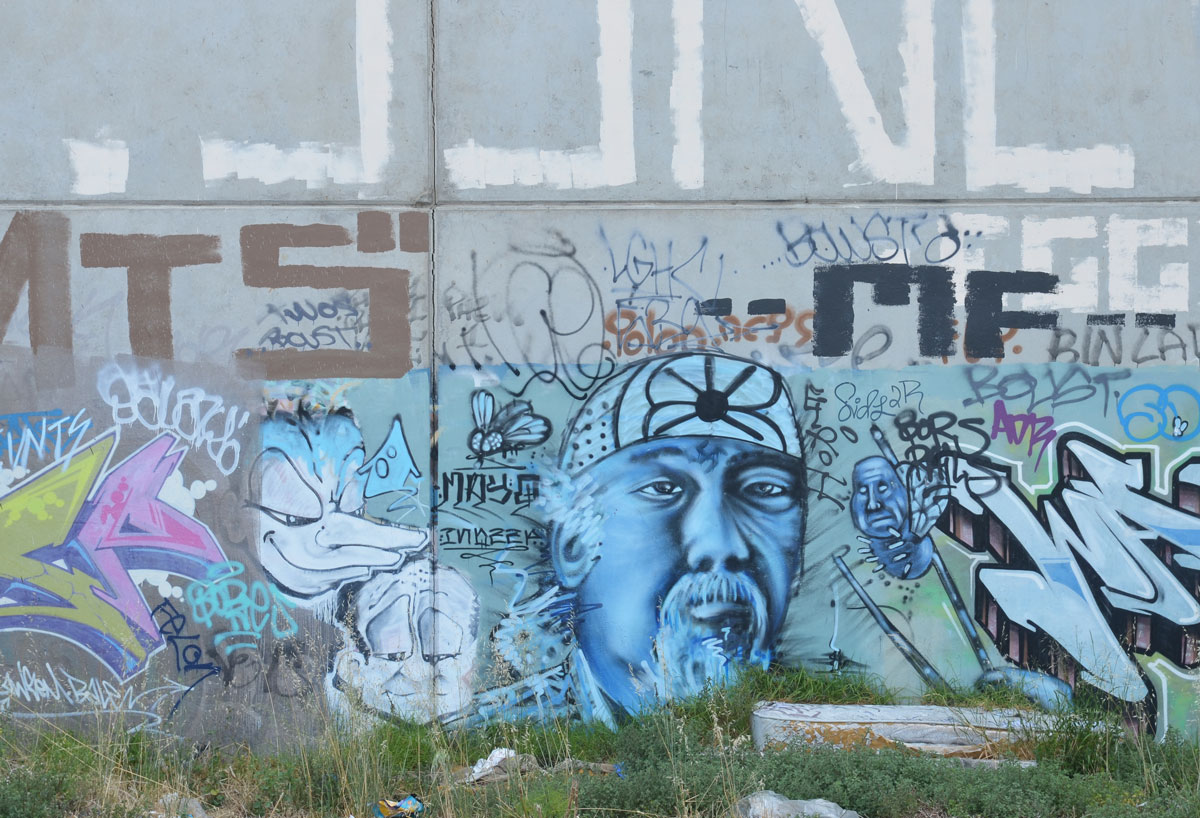 street art painting of a very blue older man's face, wearing a head band, with mustache. Three other faces are around him as well as a lot of tags