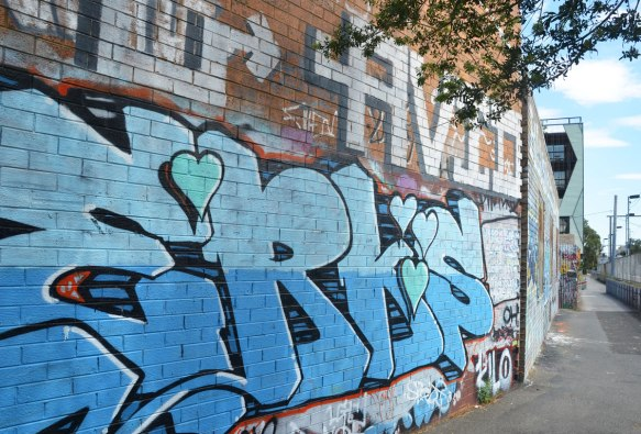 wall beside a bike path and train track, with a blue tag that includes 4 hearts