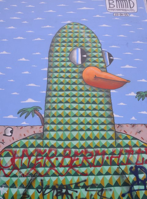 bird head on a mural, drawn with interlocking triangles in green and black, blue sky and palm trees in the background