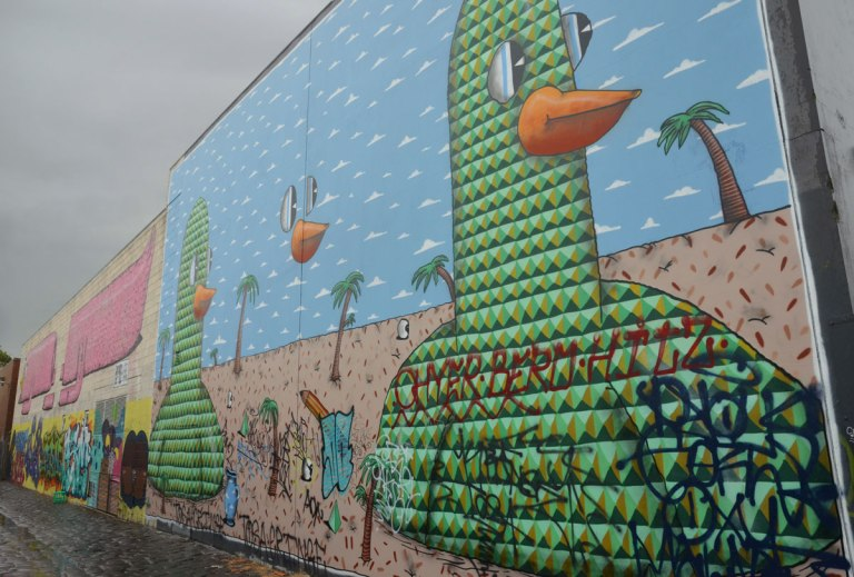 two birds on a mural, drawn with interlocking triangles in green and black, blue sky and palm trees in the background
