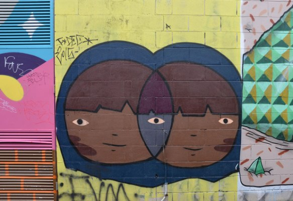 part of a larger mural, two circular girls' heads that intersect like a venn diagram