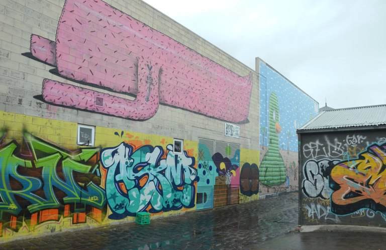 mural on a wall in alley, top part is a long pink animal and the bottom part is a text graffiti tag