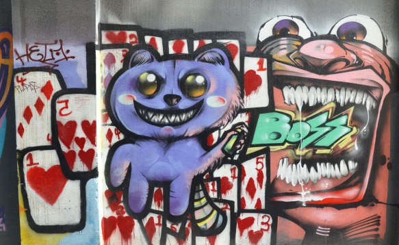 A purple cat in front of many playing cars that are hearts and diamonds. In its hand is a spray paint can, coming out from the can is the word BOSS in turquoise, the words seem to be going into a large mouth, all one street art piece in a Melbourne lane.
