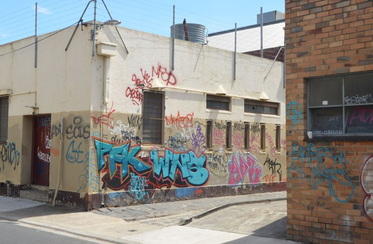 The corner of a one story white building that has a lot of graffiti on the lower half of the building.