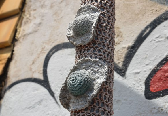 Two little grey crocheted sun hat shapes attached to a pole that is covered in beige crochet.