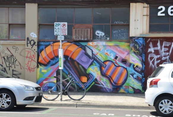 mujlti coloured mural that includes an orange and purple guitar. A bike is parked in front of the mural