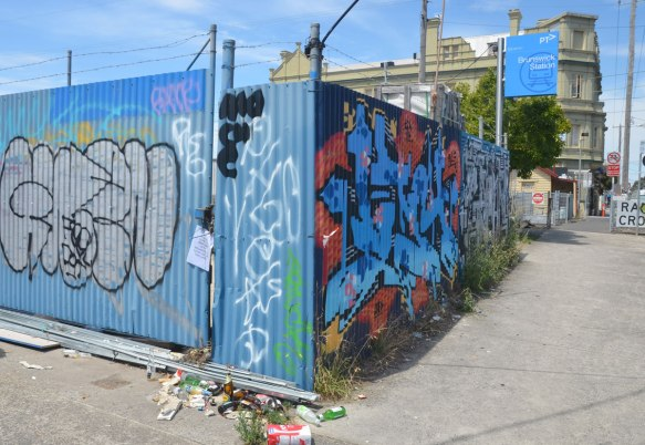 Graffiti on a corrugated metal fence. The Railway Hotel is in the background.