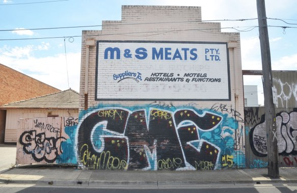 Graffiti on the lower level of M & M Meats pty ltd. C M E in large black letters on a blue background.